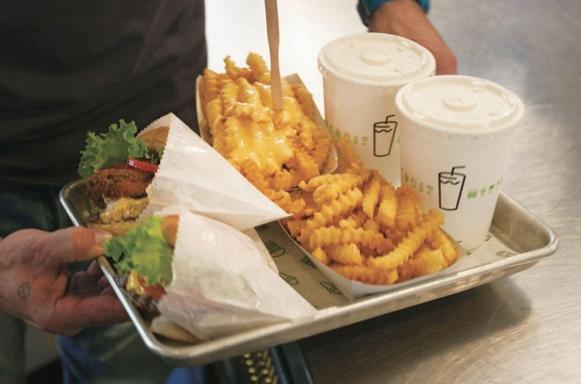 쉐이크쉑에서 주문한 음식을 받아 든 고객. 왼쪽부터 햄버거, 감자튀김, 밀크쉐이크다./블룸버그 제공