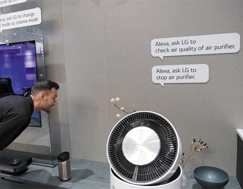 알렉사 탑재한 LG 공기청정기 - 9일(현지시각) 미국 라스베이거스에서 열린 CES 2018 행사장에서 LG전자 직원이 아마존의 인공지능(AI) '알렉사'가 탑재된 공기청정기를 작동시키고 있다. LG전자는 자체 개발한 AI 뿐 아니라 아마존·구글·네이버 등 다른 기업들이 만든 서비스도 자사 제품에 적극 탑재하고 있다.