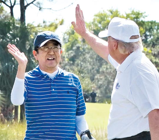아베 신조(왼쪽) 일본 총리와 도널드 트럼프 미국 대통령이 작년 2월'트럼프 내셔널 골프 클럽'에서 골프를 함께 치며 하이파이브를 하고 있다.