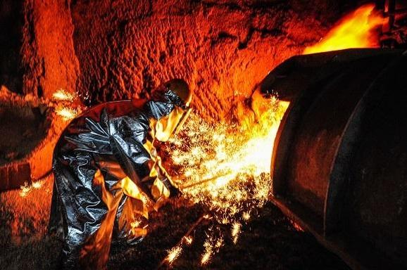 포스코 직원이 포항제철소 4고로에서 녹인 쇳물을 빼내는 출선작업을 하고 있다./포스코 제공