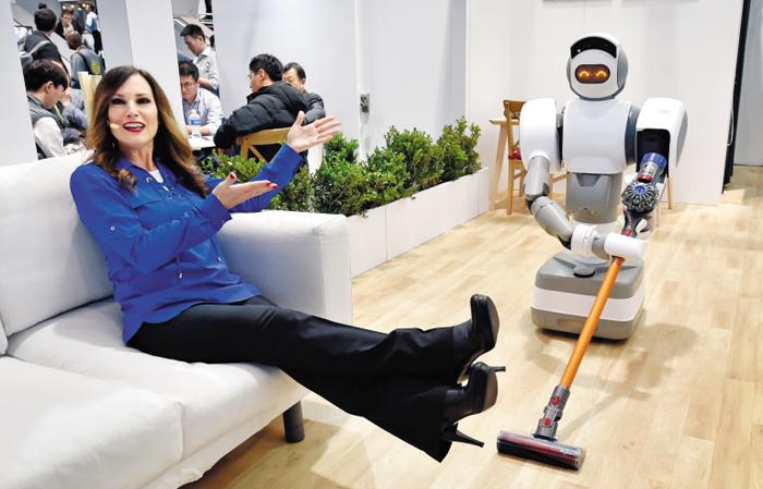 주인님, 청소하게 발 치워주세요 - 대만 스타트업 에오러스가 올해 CES에서 공개한 집사 로봇이 청소기를 팔 부분에 끼우고 바닥을 치우고 있다. 이 로봇은 머리에 달린 카메라와 인공지능을 통해 수천 가지의 물건을 구분하고 물건을 쥘 수도 있다.