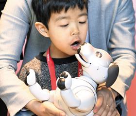 """""""로봇개야, 뽀뽀"""" - CES가 열린 미국 라스베이거스 컨벤션센터에서 남자 아이가 소니의 로봇 강아지 '아이보'를 품에 안고 입을 맞추려 하고 있다."""