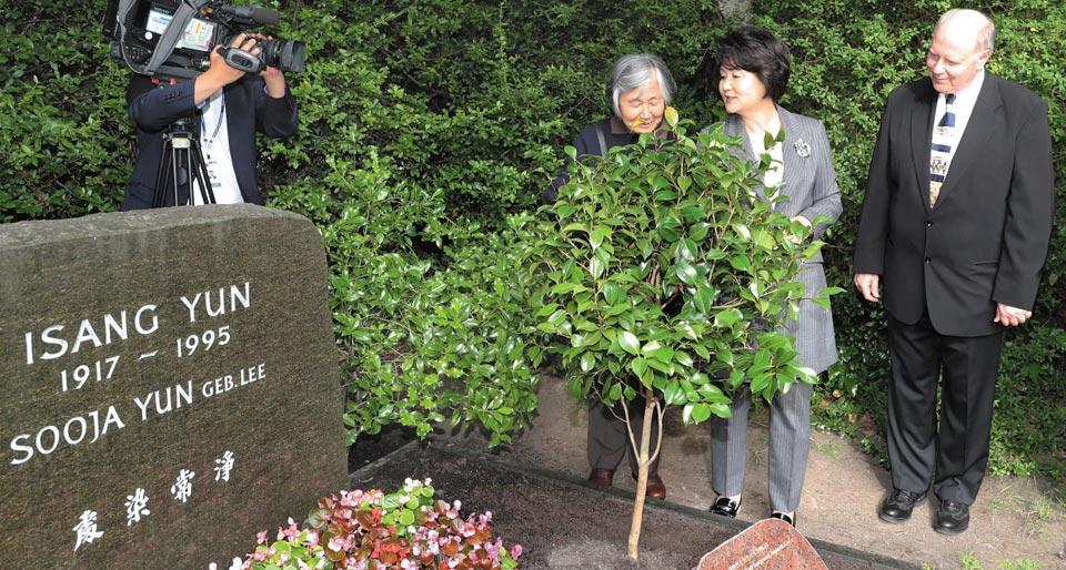 2017년 7월 김정숙 여사가 독일 베를린에 안장된 작곡가 윤이상씨의 묘소를 찾아 통영에서 옮겨 심은 동백나무를 보고 있다.