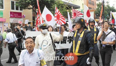 """5년 전에는… - 2013년 9월 8일 120여명이 도쿄 신주쿠구 신오쿠보 인근 거리에서 """"한국인은 나가라"""" 등 혐한(嫌韓) 구호를 외치며 행진하고 있다."""