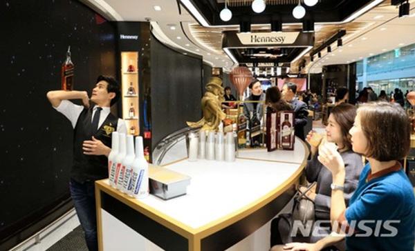 18일 인천공항 제2여객터미널에 오픈한 롯데면세점을 찾은 고객들이 주류·담배 플래그십 매장에서 전문 바텐더의 공연을 보며 칵테일 시음을 하고 있다.