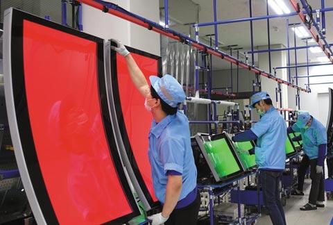 인천 연수구 송도에 있는 코텍의 카지노 모니터 제조 라인에서 직원들이 43인치(약 109㎝) 커브드(곡면) 모니터를 검사하고 있다.
