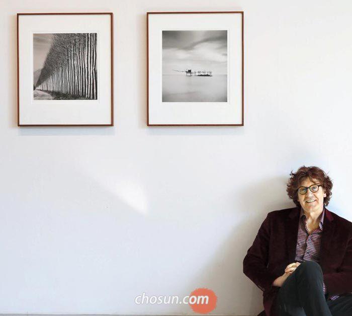 이탈리아에서 찍은 작품 아래 앉아 있는 마이클 케나.