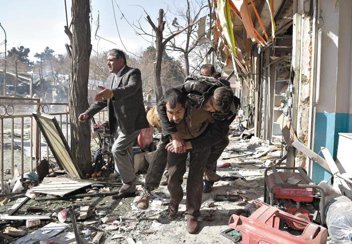 27일(현지 시각) 아프가니스탄 수도 카불 도심에서 발생한 차량 폭탄 테러로 부상당한 사람을 시민들이 업어 옮기고 있다.