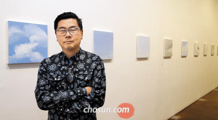 서울 삼청동 국제갤러리에 걸린 '일요일 회화' 연작 앞에 선 바이런 킴. 2007년부터 2016년까지 그린 하늘 중 한국 또는 여행과 관련된 작품을 골랐다.