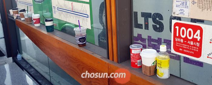 서울 아현역 인근 버스 정류장 간이 벤치에 음료잔이 늘어서 있다. 버스 기사가 음료수 반입을 거부할 수 있게 되자 사람들이 컵을 버리고 탑승한다.