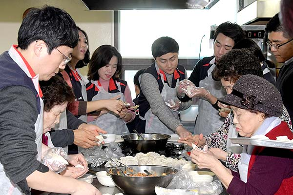 KT IS 임직원이 센터 어르신들과 만두빚기, 밑반찬 만들기를 하고 있다.