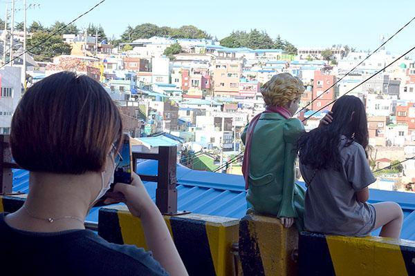 감천문화마을을 방문한 관광객이 어린왕자 조형물과 기념사진을 찍고 있다.