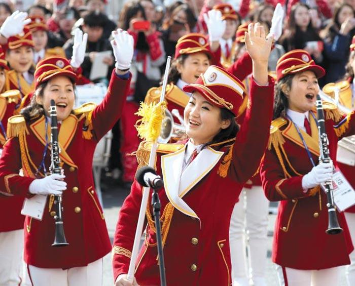 공연 북한 응원단원들이 8일 강원도 강릉 선수촌에서 열린 평창 동계올림픽 북한 선수단 입촌식에서 관악기를 들고 축하 공연을 하며 관람객들을 향해 손을 흔들고 있다.
