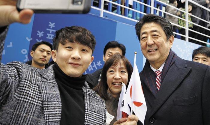 아베 신조(맨 오른쪽) 일본 총리가 10일 평창올림픽 여자 아이스하키 경기가 열린 강원도 강릉 관동하키센터를 찾아 관중들의 사진 촬영 요청에 응하고 있다.