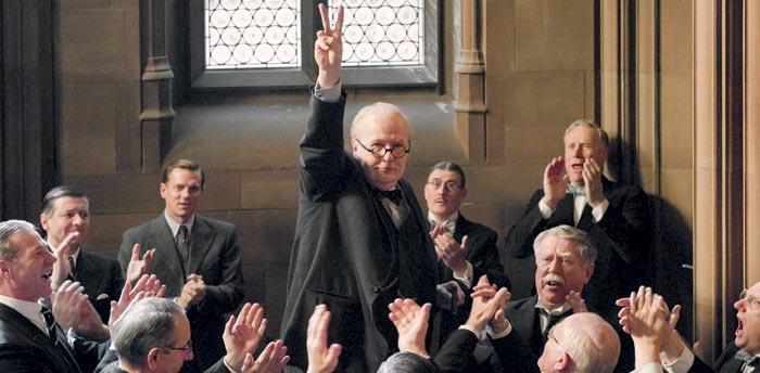 """영화'다키스트 아워'에서 처칠이""""우린 꺾이지 않을 것입니다. 끝까지 싸울 것입니다""""라고 외치고 나서 손가락으로 승리의 V를 만들어 보이는 모습."""
