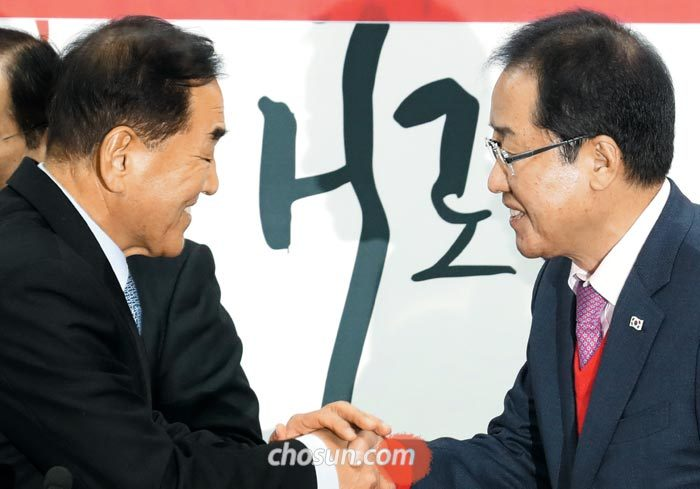 자유한국당 홍준표(오른쪽) 대표가 12일 오전 서울 여의도 당사에서 열린 입당 행사에서 이재오 전 의원과 악수를 하고 있다.