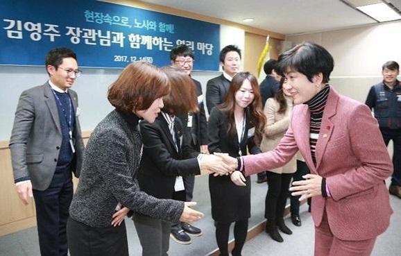 김영주(오른쪽) 고용노동부 장관이 작년 12월 14일 서울 마포에 있는 노사발전재단을 방문해 직원들과 악수하고 있다./고용노동부 제공