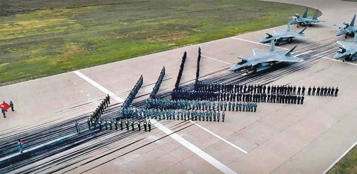 중국 신형 전투기 젠(殲)-20과 젠-16 앞에 도열한 중국 조종사들. 중국 군사 전문 매체 신랑군사망은 14일 스텔스 기능을 갖춘 젠-20 전투기를 산둥반도 등 군 기지 3곳에 우선 배치했다고 보도했다.