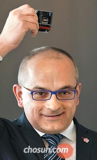 파스칼 헤리티에 세가프레도자네티 최고경영자(CEO)가 자사 카페에서 사용하는 에스프레소 잔을 머리 위로 들어 올려 보이고 있다.