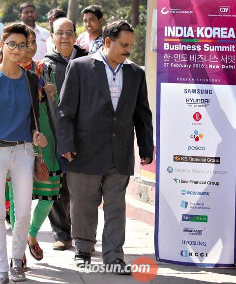 '제2회 한·인도 비즈니스 서밋' 개막을 하루 앞둔 26일 인도 뉴델리 중심부 센트럴 시크리테리엇역 입구에 설치된 행사 광고판 옆으로 시민들이 지나가고 있다.