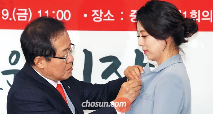 자유한국당 홍준표 대표가 9일 서울 여의도 당사에서 입당식을 가진 배현진 전 MBC 아나운서에게 태극기 배지를 달아주고 있다
