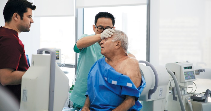 안강병원의 안강 원장이 쿠웨이트 안강병원에서 이학적 검사로 어깨 통증 환자를 살피고 있다.