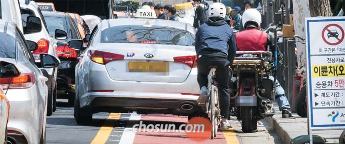 서울 종로 자전거 전용차로 개통 이틀째인 9일 서린동 인근에서 전용차로로 달리던 자전거 운전자가 불법 침범한 택시와 오토바이에 막혀 정차해 있다. 이날 기자가 달려본 전용차로는 30초마다 한 번씩 생명의 위협을 느끼는 위험한 도로였다.