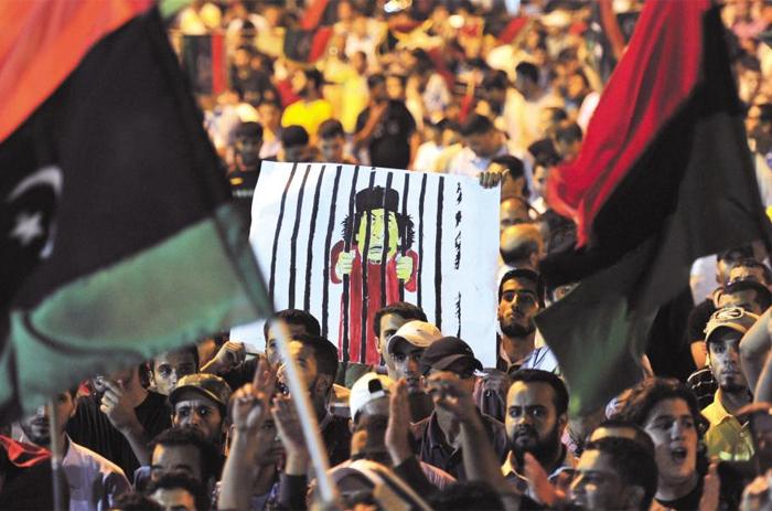 2011년 8월 22일 리비아 시민군이 수도 트리폴리에 입성하자 저항 세력의 거점도시인 벵가지 주민들이 카다피가 감옥에 갇혀 있는 그림을 들고 거리에 나와 환호하고 있다.