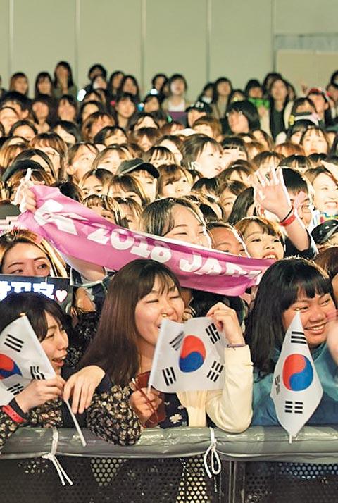 13일 일본 지바시 마쿠하리 멧세 전시장에서 열린 한류 페스티벌 케이콘에 참석한 일본 관객들이 태극기를 흔들며 환호하고 있다.