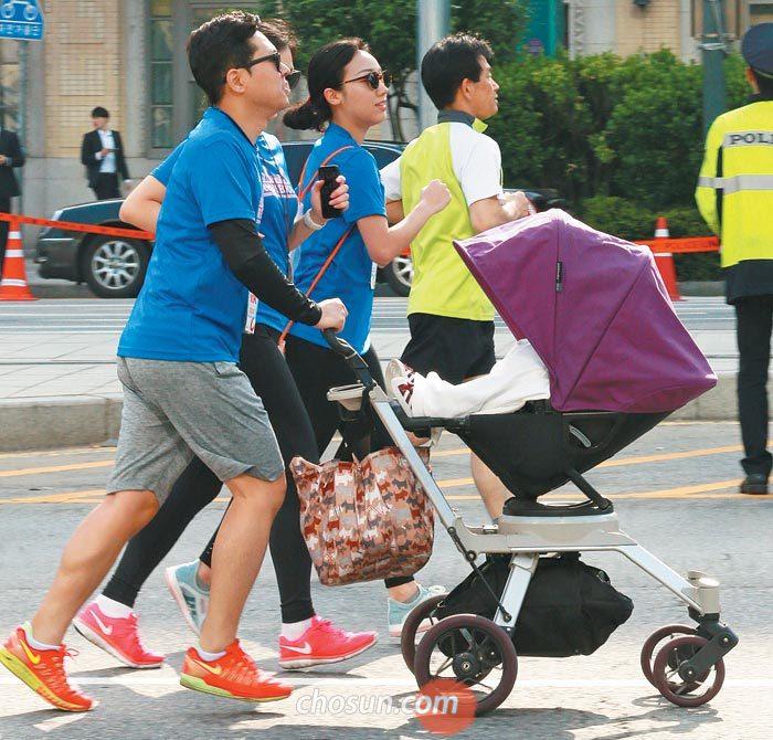 한 가족 참가자가 유모차를 밀며 달리는 모습.