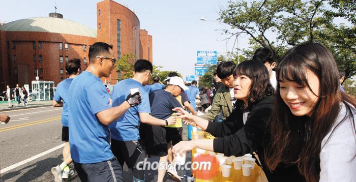 29일 '2018 서울하프마라톤'이 열린 서울 여의도순복음교회 앞에서 이 교회 자원봉사자들이 물과 음료를 나눠주고 있다.