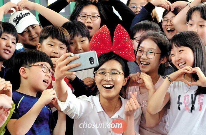 스승의 날을 하루 앞둔 14일 대전 둔산초등학교 5학년 4반 학생들이 손으로 하트 모양을 그리면서 담임선생님과 기념사진을 찍고 있다.