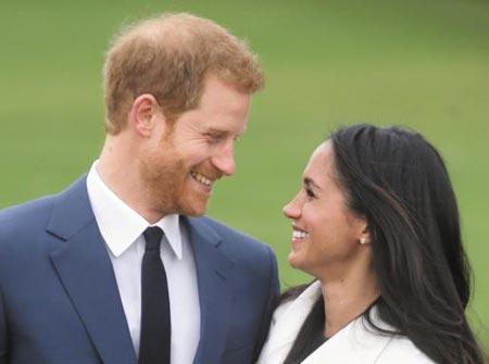 해리 왕자와 메건 마클이 지난해 11월 영국 런던 켄싱턴궁에서 약혼을 발표하고 나서 마주보며 웃고 있다.