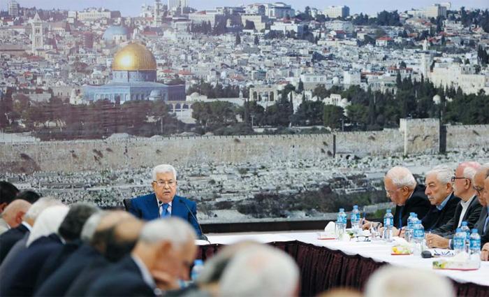 """팔레스타인 수반, 이스라엘 규탄하지만… - 마무드 압바스 팔레스타인 자치정부 수반(가운데)이 14일(현지 시각) 팔레스타인 임시 수도 라말라에서 지도부 회의를 열고 이스라엘을 규탄하는 발언을 하고 있다. 이날 이스라엘군이 미국 대사관의 예루살렘 이전에 항의하는 팔레스타인 시위대에게 실탄을 발사해, 시위자 61명이 숨지고 2700여명이 다쳤다. 압바스는 """"팔레스타인 국민을 상대로 저지른 대학살""""이라고 비난했다. 압바스 수반 뒤로 예루살렘의 전경을 담은 커다란 벽 사진이 보인다. 팔레스타인은 동(東)예루살렘을 미래 자국의 수도로 주장하고 있다."""