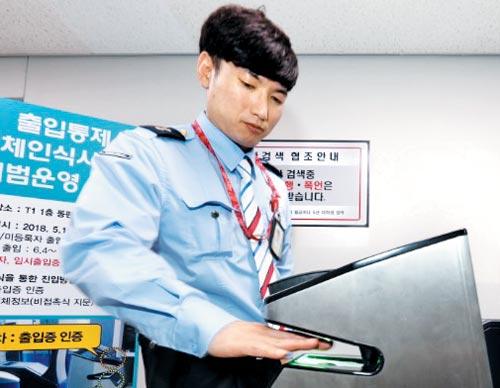 16일 인천공항 1터미널 상주 직원 출입구에 시범 도입된'비접촉 지문 인식 기기'에 인천공항공사 직원이 손을 집어넣으며 시연하고 있다.