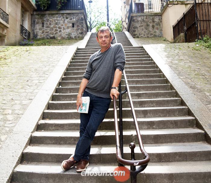 """작업실이 있는 파리 몽마르트르 인근의 골목길에 선 피에르 르메트르. """"소설이 성공할수록 독자를 실망시킬까 봐 겁난다""""면서도 """"내가 재밌는 이야기를 택할 뿐 독자의 선호는 고려치 않는다""""고 말했다."""