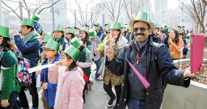 지난 4월 서울로 7017에서 열린 퍼레이드 축제 '봄나팔 대행진'에서 초록 모자를 쓴 외국인 방문객과 시민들이 나팔을 불며 축제를 즐기고 있다. 지금까지 약 200만 명의 외국인이 서울로를 다녀갔다.