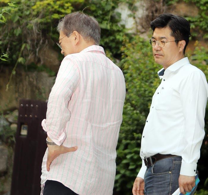 지난해 5월 21일 경남 양산시 사저를 찾은 문재인(왼쪽) 대통령이 송인배 청와대 제1부속비서관이 건넨 전화기를 들고 통화를 하고 있다.