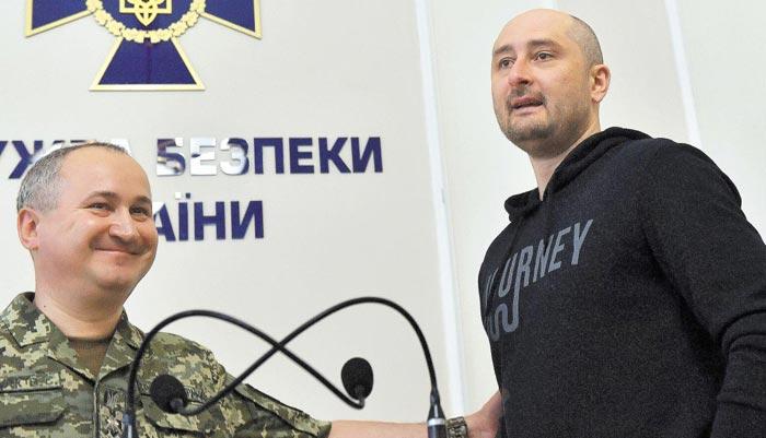 우크라이나에서 총에 맞아 피살된 것으로 알려졌던 아르카디 바브첸코(오른쪽) 러시아 기자가 30일(현지 시각) 우크라이나 수도 키예프에서 보안당국 관계자의 소개로 기자회견장에 나오고 있다.