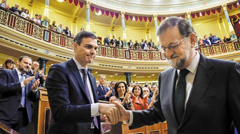 1일(현지 시각) 스페인 국회의사당에서 신임 총리가 된 페드로 산체스(왼쪽) 사회당 대표가 총리직에서 물러난 마리아노 라호이(오른쪽) 전 총리와 악수하고 있다.