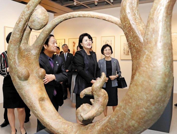 5일 개막식에 온 김정숙 여사가 한메이린의 청동조각상'엄마와 아들'을 관람하고 있다.