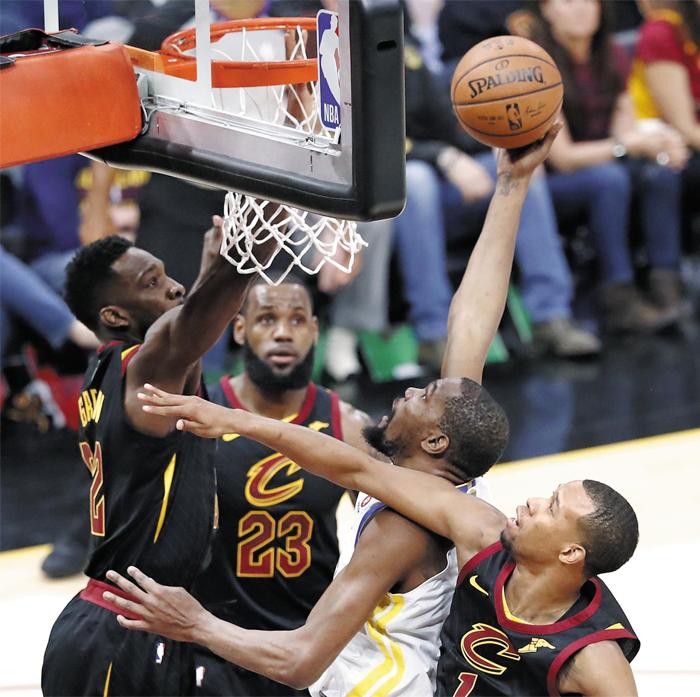 듀랜트, 3명 제치고 슛 - NBA 챔피언결정전 3차전에서 골든스테이트 워리어스 승리를 이끈 영웅은 케빈 듀랜트(흰색 상하의)였다. 듀랜트가 캐벌리어스 수비 숲 사이로 솟아올라 슛을 시도하는 모습. 이날 그는 43점을 쏟아 부으며 팀의 파이널 3연승을 이끌었다.