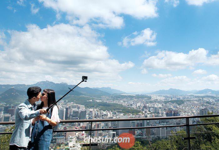 여름 하늘이 말간 얼굴을 드러낸 12일 오전 서울 남산타워에서 한 쌍의 남녀가 자신들이 입맞춤하는 장면을 셀카봉으로 촬영하고 있다.