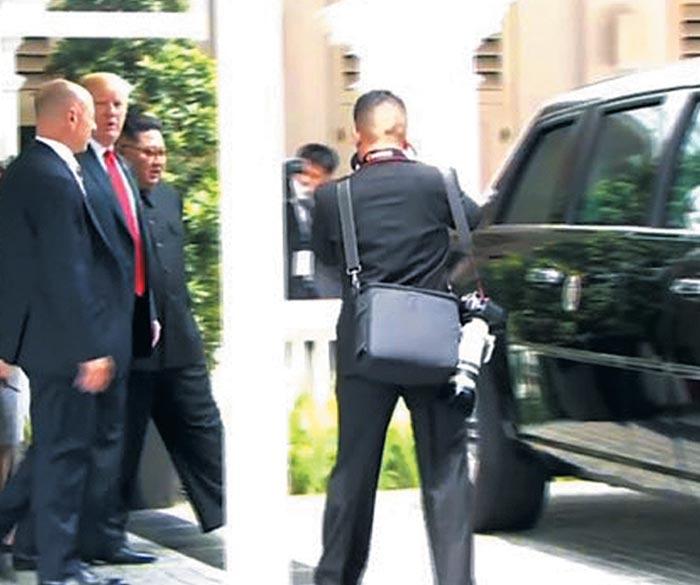 트럼프 대통령이 12일 김정은 국무위원장과 카펠라호텔 경내를 산책한 뒤 자신의 전용 차량인'캐딜락 원'으로 향하고 있다.