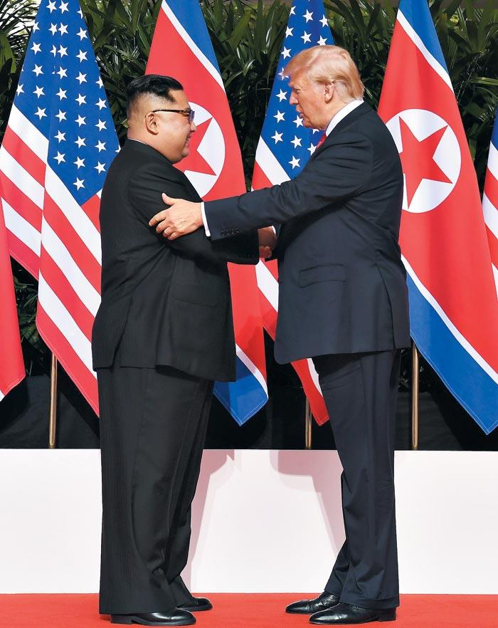 도널드 트럼프 미국 대통령과 김정은 북한 국무위원장이 12일 첫 인사를 나누고 있다.