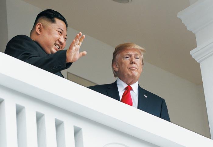 김정은 위원장과 도널드 트럼프 대통령이 12일 싱가포르 카펠라 호텔 발코니에서 단독정상회담을 마친 뒤 취재진들에게 인사하고 있다.