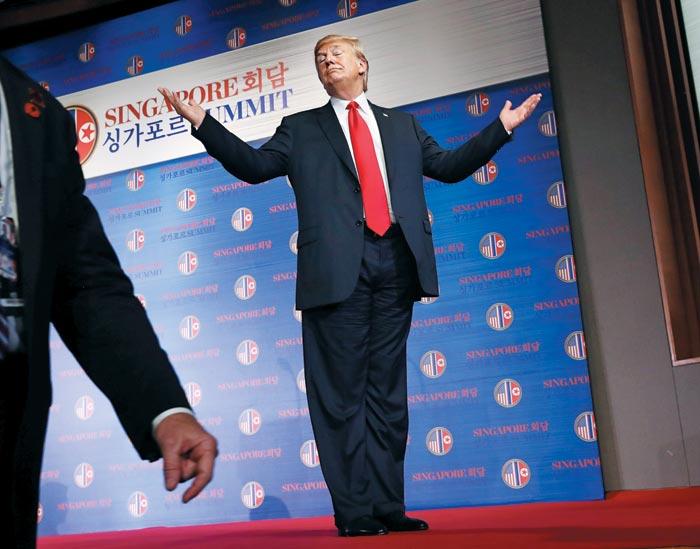 도널드 트럼프 미국 대통령이 12일 오후 싱가포르 카펠라 호텔에서 기자회견을 마친 후, 정부 관계자 등이 수고했다며 박수를 치자 자랑스럽게 으쓱하는 제스처를 취하고 있다.