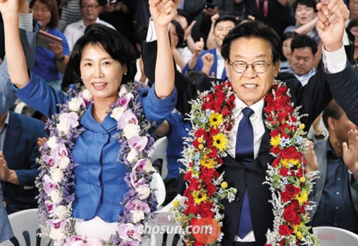 더불어민주당 이재명 경기지사 후보와 아내 김혜경씨가 13일 경기도 수원시 팔달구 선거사무소에서 꽃다발을 목에 걸고 손을 높이 들고 있다.