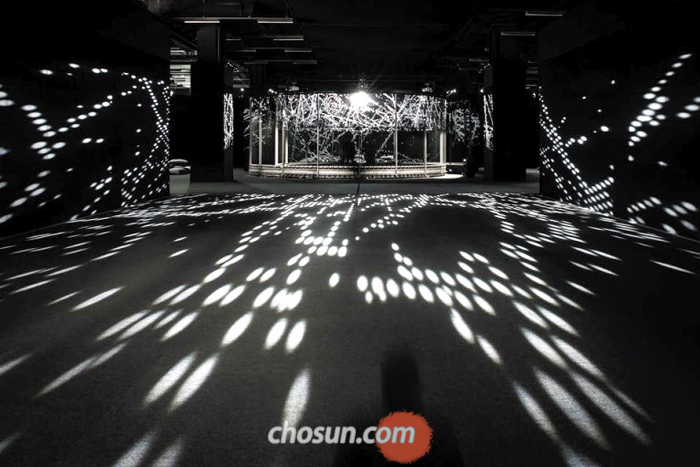 스위스 아트 바젤에서 화제가 된 대형 설치작품 '헤일로'. 2인조 아티스트 '세미컨덕터'와 유럽입자물리연구소(CERN)가 협업해 만들었다. 원통형 구조물에 피아노 줄을 달아 입자의 충돌을 빛과 소리로 표현했다.