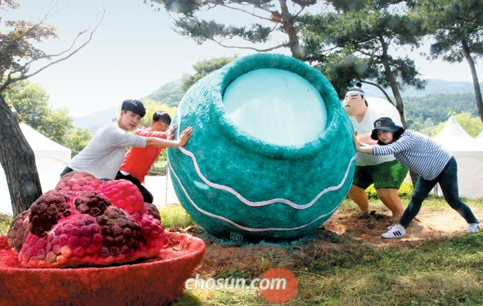 지난 20일 오후 전북 고창의 관광객들이 엎어진 요강을 본뜬 조형물을 일으켜 세우는 동작을 하고 있다.